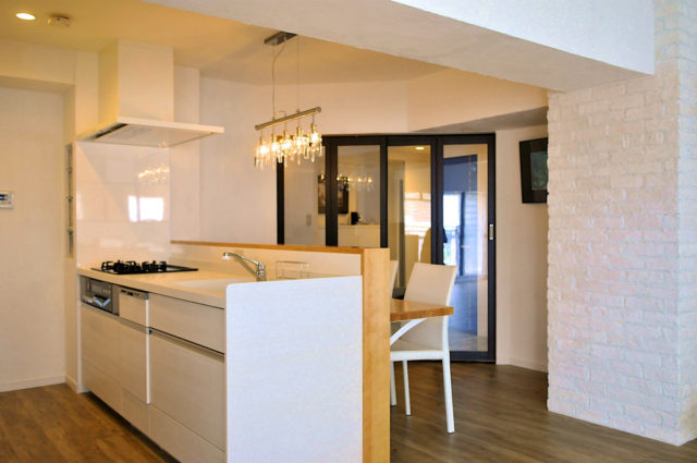 真っ白なキッチンの対面には食事も出来るカウンターを配置