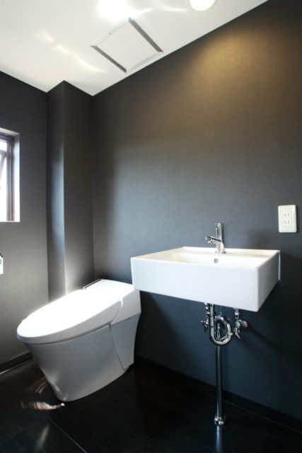 床と壁を黒にして、トイレと洗面を一体にしたスタイリッシュな洗面脱衣室