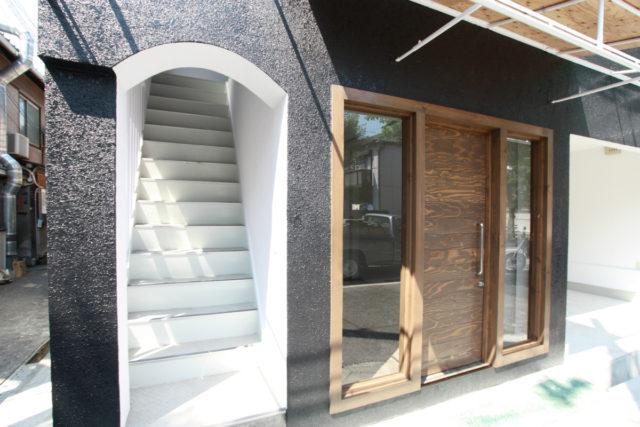 外壁を黒と白に塗り分け、1Fにはパーキングとギャラリーを併設