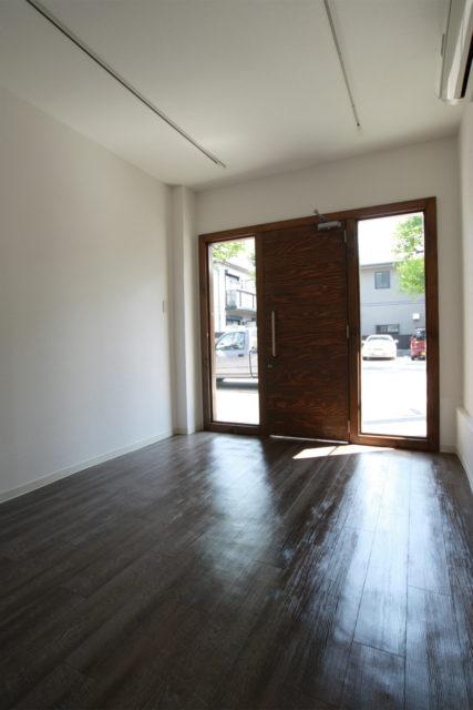 濃い色の床と白い壁のコントラストが映える、明るい日差しの入るギャラリー