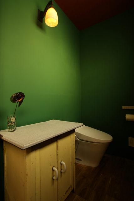 緑の壁に、アンティークの照明と家具が映える