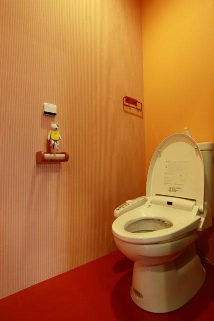 赤のアクセントのきいた明るいトイレ