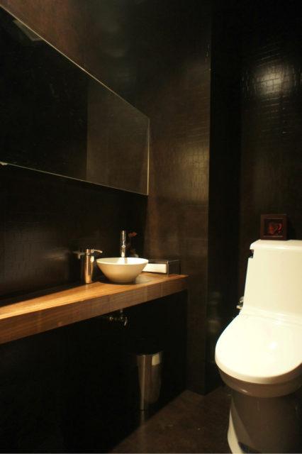 黒のクロコ柄で覆われた非日常なトイレ空間