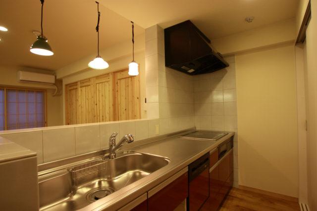 アンティークのペンダントが映えるタイル壁のキッチン